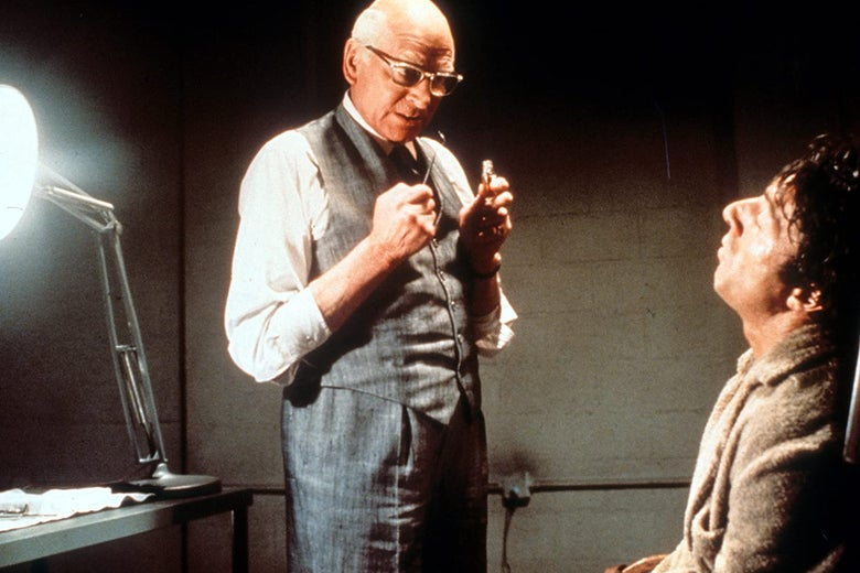 Laurence Olivier stands over Dustin Hoffman holding dental tools.