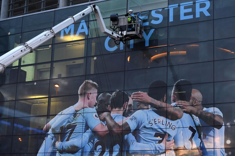A workman begins to change the external panel designs on the Etihad Stadium in Manchester.