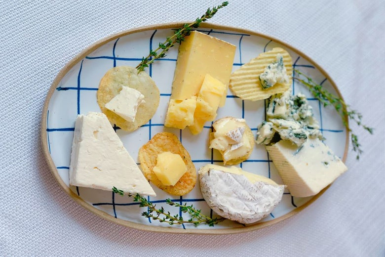 A variety of potato chips and cheeses on a platter with herbs.