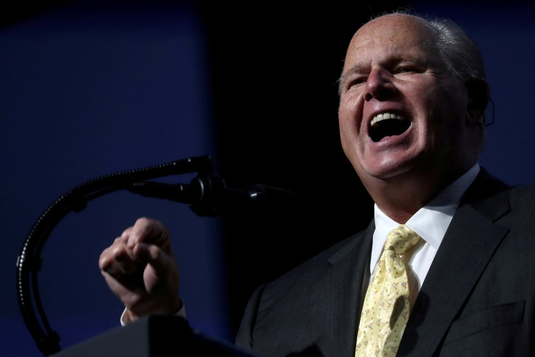 Rush Limbaugh points and speaks into a microphone.