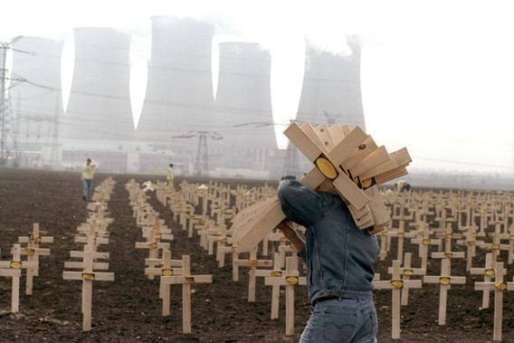 A Greenpeace activist carries several of 3000 wooden crosses to be set up in front of the Soviet-built nuclear power plant in Bohunice, April 25, 1991 to commemorate the nuclear disaster in Chernobyl five years earlier.