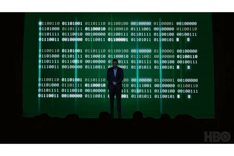 Matt Ross standing in front of a screen full of binary code.