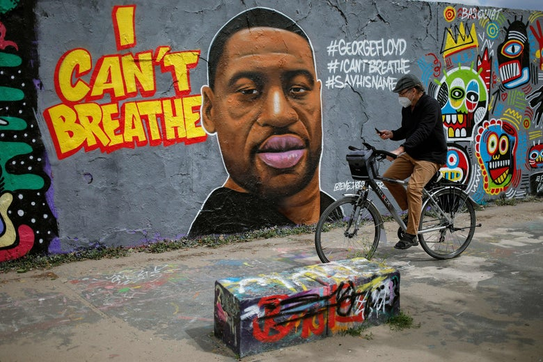 A man wearing a face mask looks at his phone as he cycles passed a graffiti on a wall depicting a portrait of George Floyd, a black man who died in Minneapolis after a white policeman kneeled on his neck for several minutes, is seen on a wall at Mauer Park in Berlin's Prenzlauer Berg district on May 30, 2020.