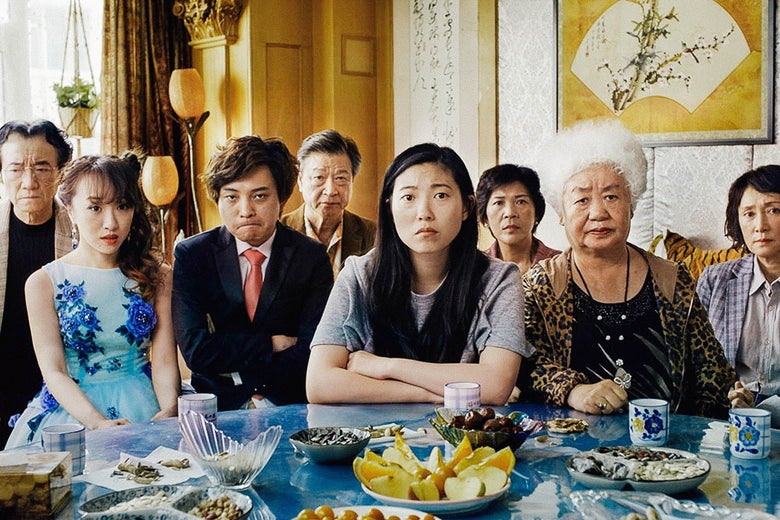 The cast of The Farewell sits at a table in a film frame.