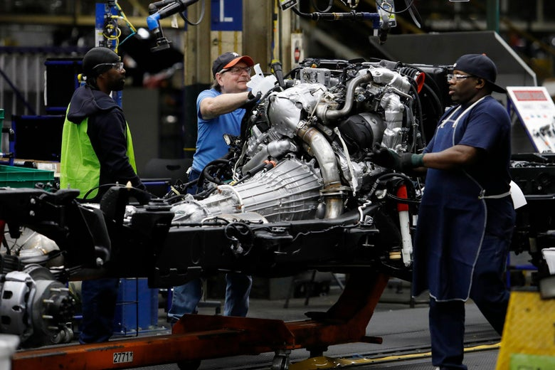 Line workers work on the chassis of full-size General Motors pickup trucks at the Flint Assembly plant on June 12, 2019 in Flint, Michigan.