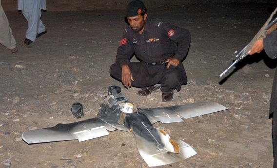 Pakistani security personnel examine a crashed American surveillance drone.