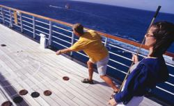 Couple playing shuffleboard on cruise ship deck.