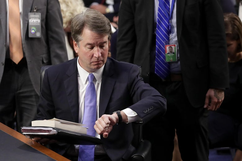 Brett Kavanaugh, wearing a blue tie and holding a bundle of papers, looks at his watch.