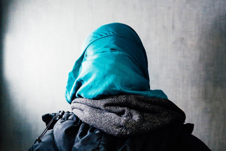 The back of the head of a woman wearing a headscarf, hoodie, and jacket.