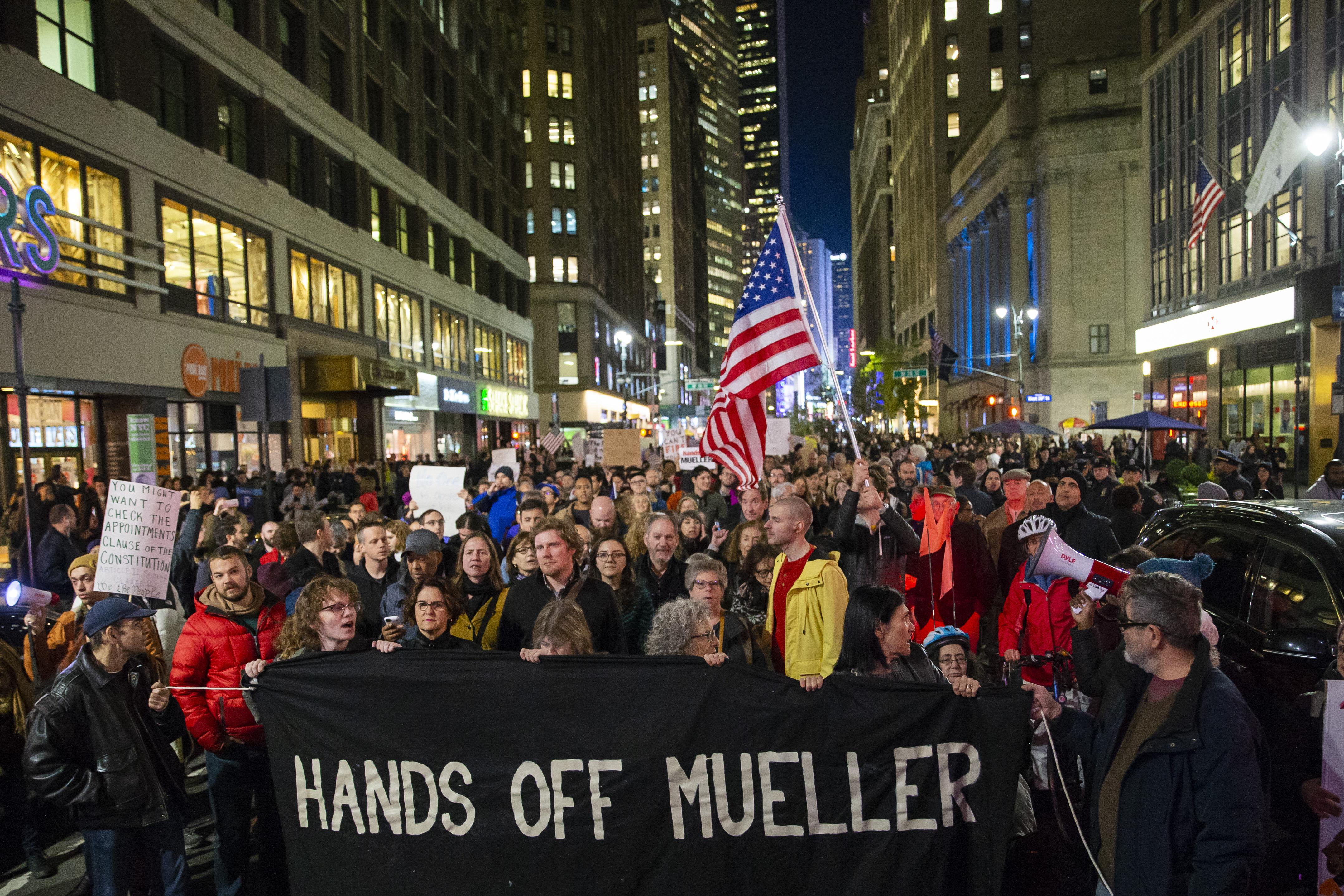 """Protesters walk through Times Square with a banner that says """"Hands Off Mueller."""""""