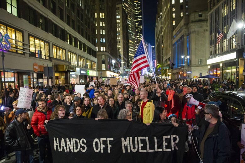"Protesters walk through Times Square with a banner that says ""Hands Off Mueller."""