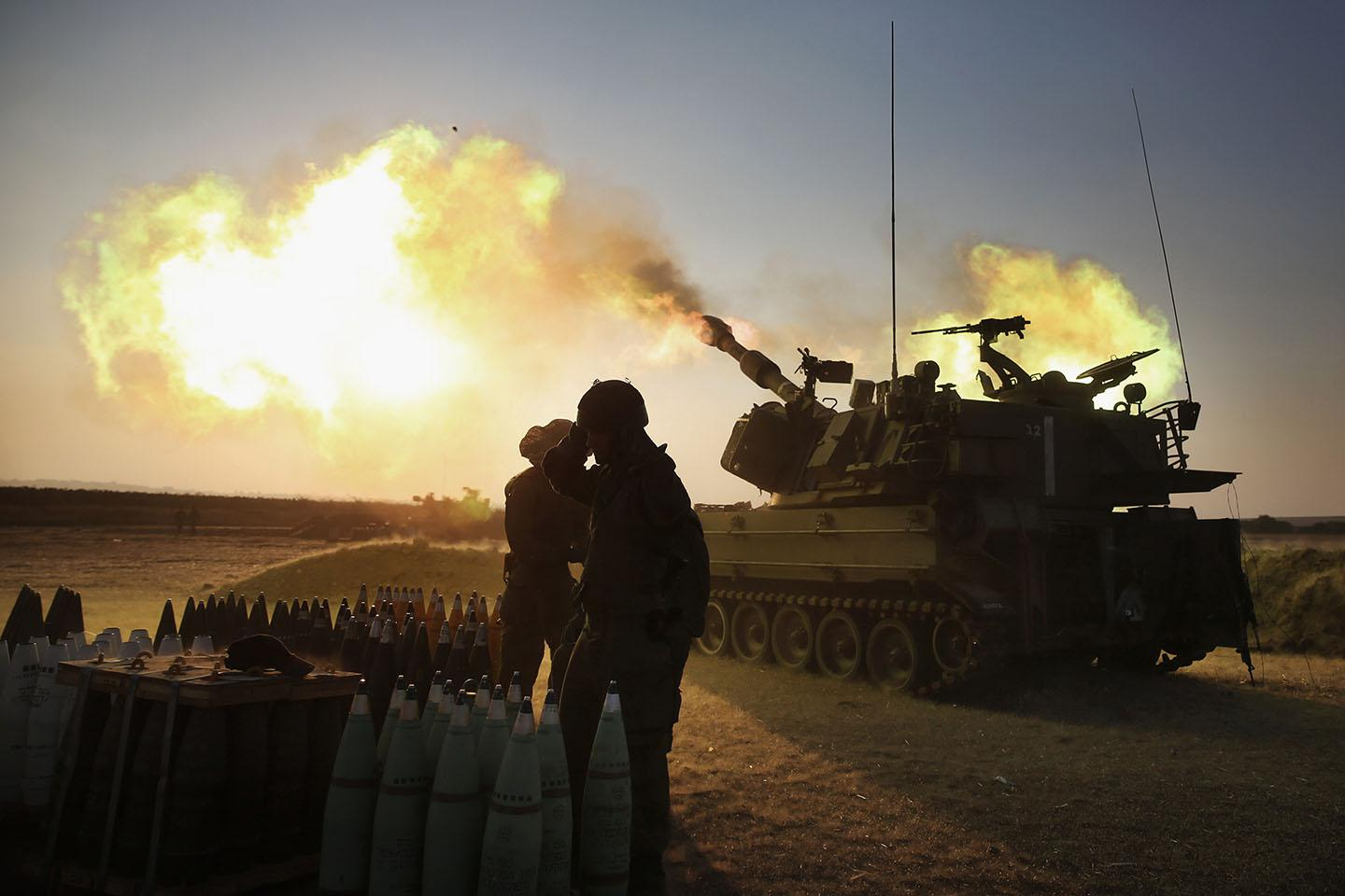 Israeli soldiers of the 155mm artillery cannons unit fire towards the Gaza Strip.