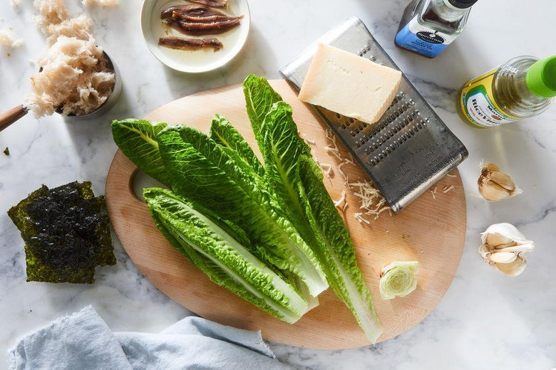 On a counter: Romaine lettuce, seaweed, anchovies, garlic, rice vinegar and sesame oil. A block of parmesan cheese sits atop a grater.