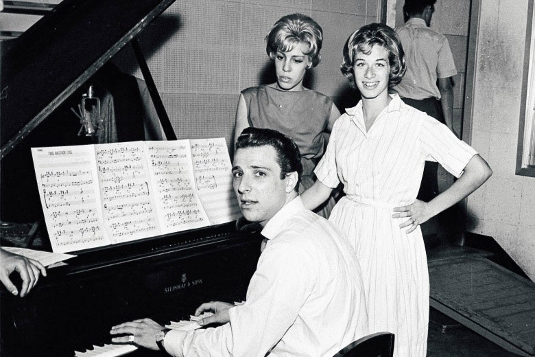 Barry Mann sitting at the piano, with Cynthia Weil and Carole King standing next to him.