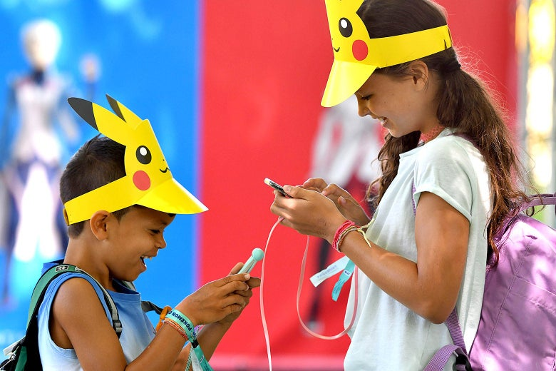 Switzerland's Leo, 9, and his sister Lea, 10, look at their phones during the Pokemon Go Festival on July 4, 2019 at the Westfalenpark in Dortmund, western Germany.