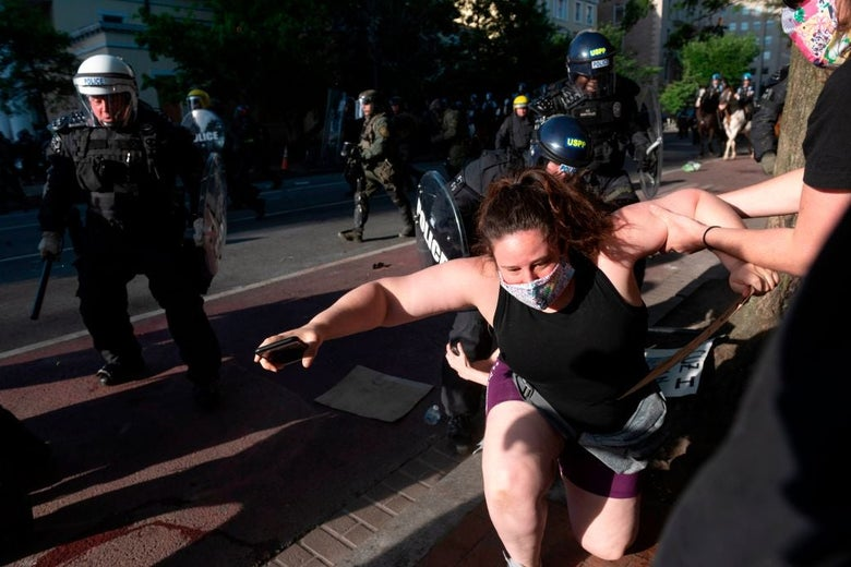 An unassuming woman wearing shorts and a tank top appears to stumble as she is pulled away from onrushing police carrying clubs and shields.