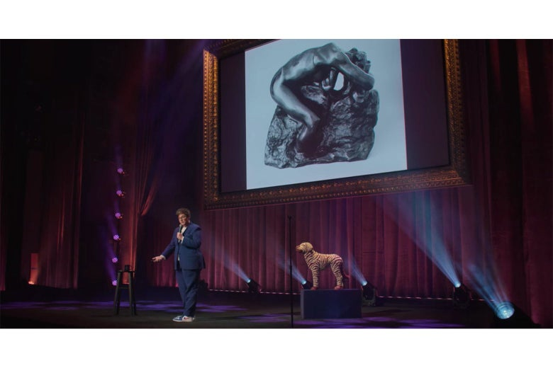 Hannah Gadsby stands in front of a photograph of a Rodin bronze of Andromeda.