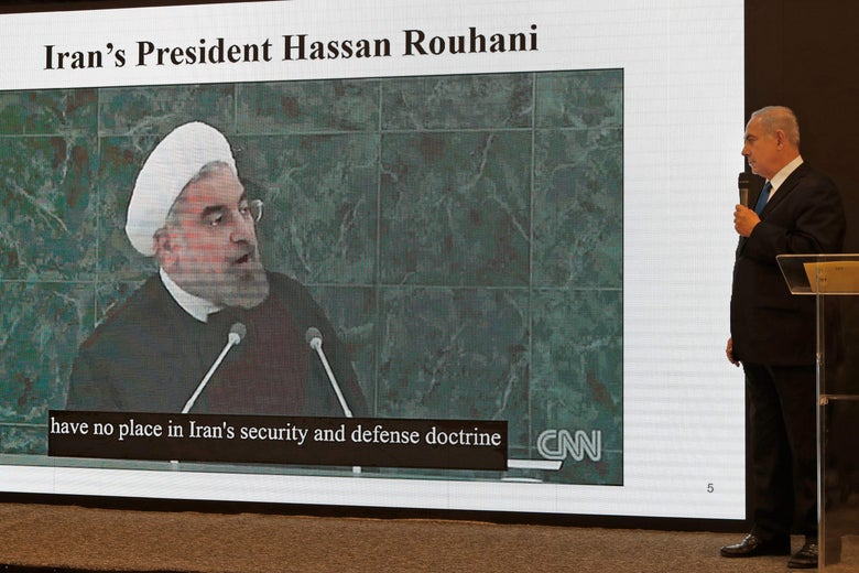 Israeli Prime Minister Benjamin Netanyahu delivers a speech with a slide of Iranian President Hassan Rouhani behind him.