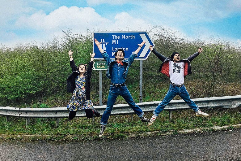 The three characters jump for joy in front of a road sign in a still from the movie.