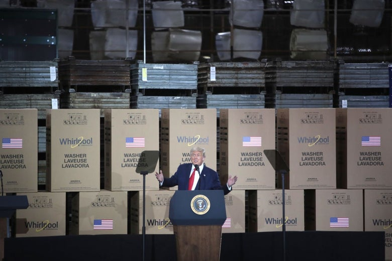 Trump gives a speech against a backdrop of boxed-up washing machines and stacks of what appear to be metal sheets.
