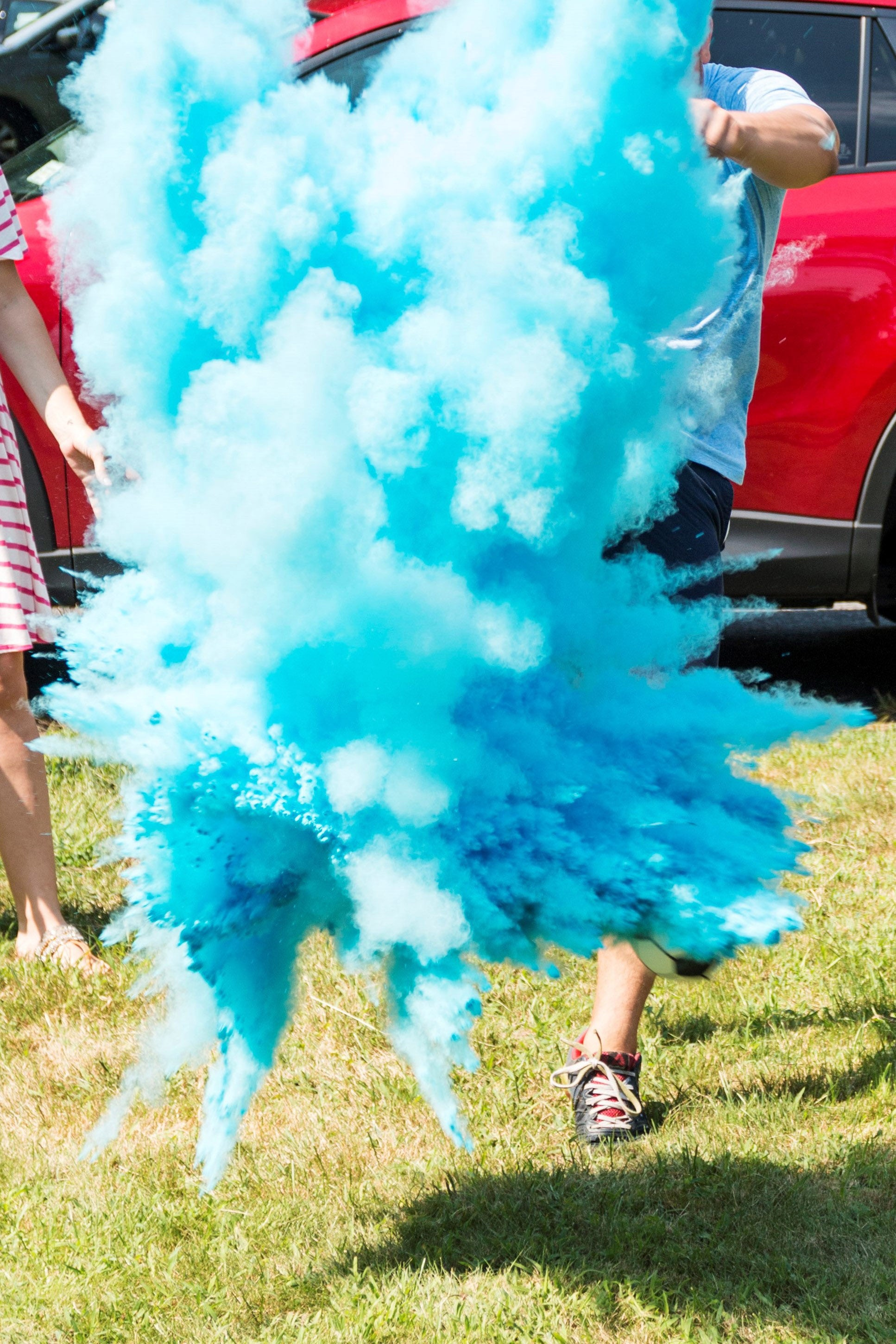 A man blowing himself up with blue gender smoke.