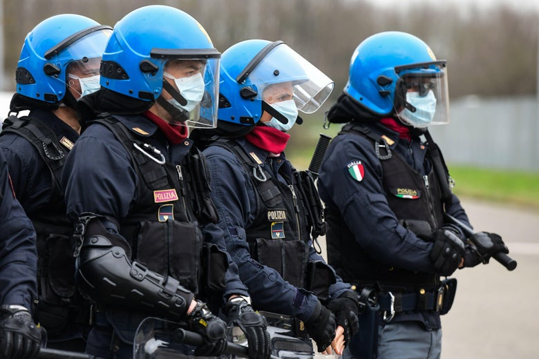 Police officers wearing protective face masks stand in a line.