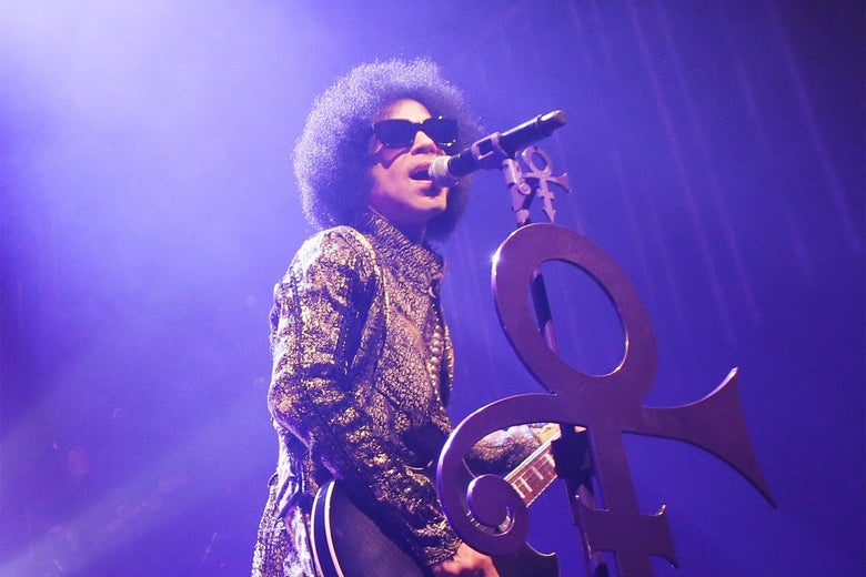 Prince performs in front of a microphone with the Love Symbol, bathed in purple lighting.