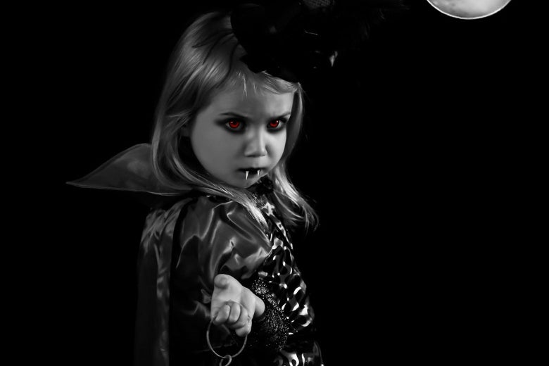 A toddler with red eyes and vampire fangs.
