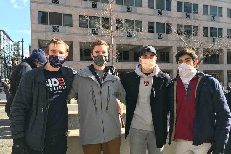 Four college-age men stand outside in downtown D.C.