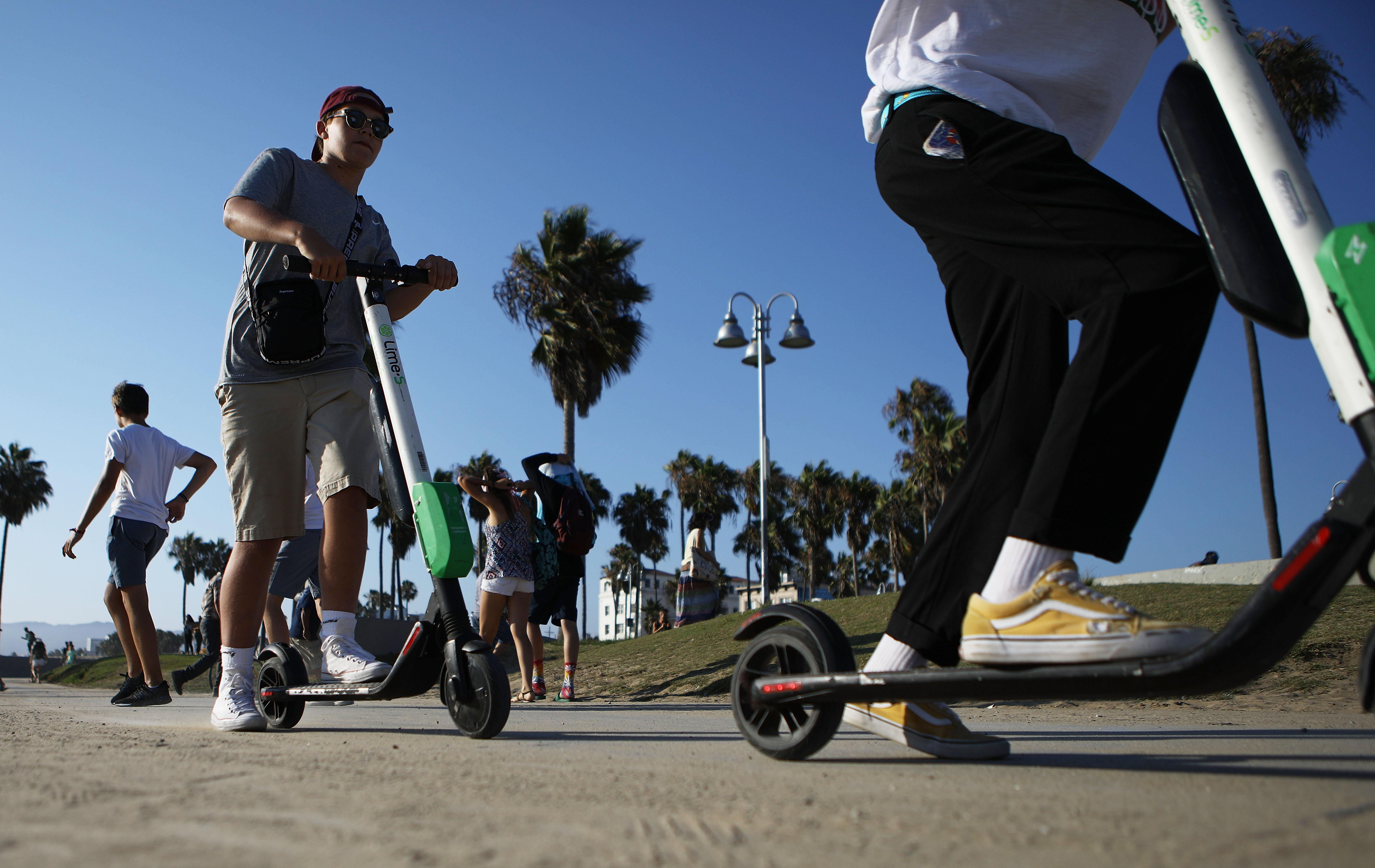 Two people ride Lime shared dockless electric scooters along Venice Beach on August 13, 2018 in Los Angeles, California.
