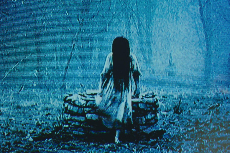A grainy, blue-tinged image of a girl with long black hair covering her face. She wears a nightgown.