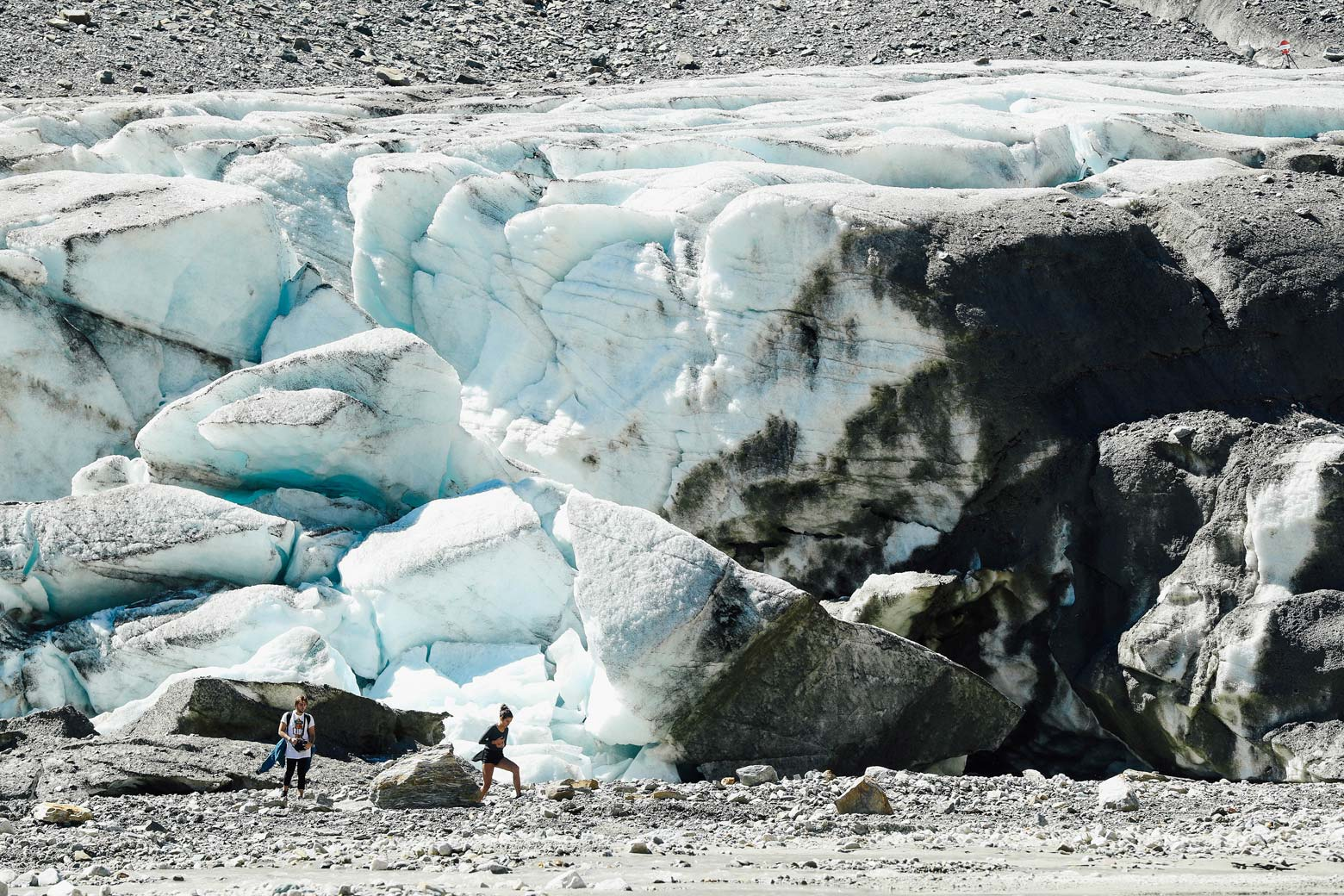 Visitors walk past collapsing, melting ice.