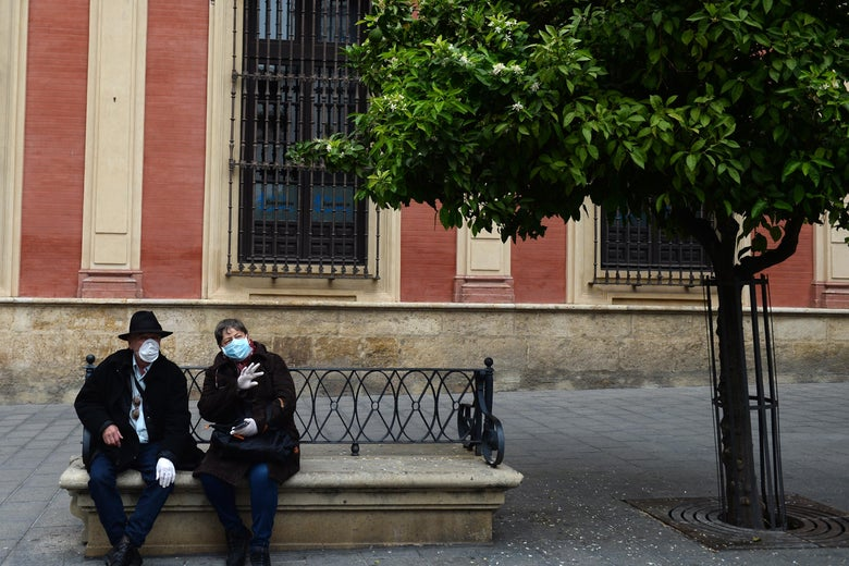 A couple, wearing protective masks and gloves, sit on a bench outside.