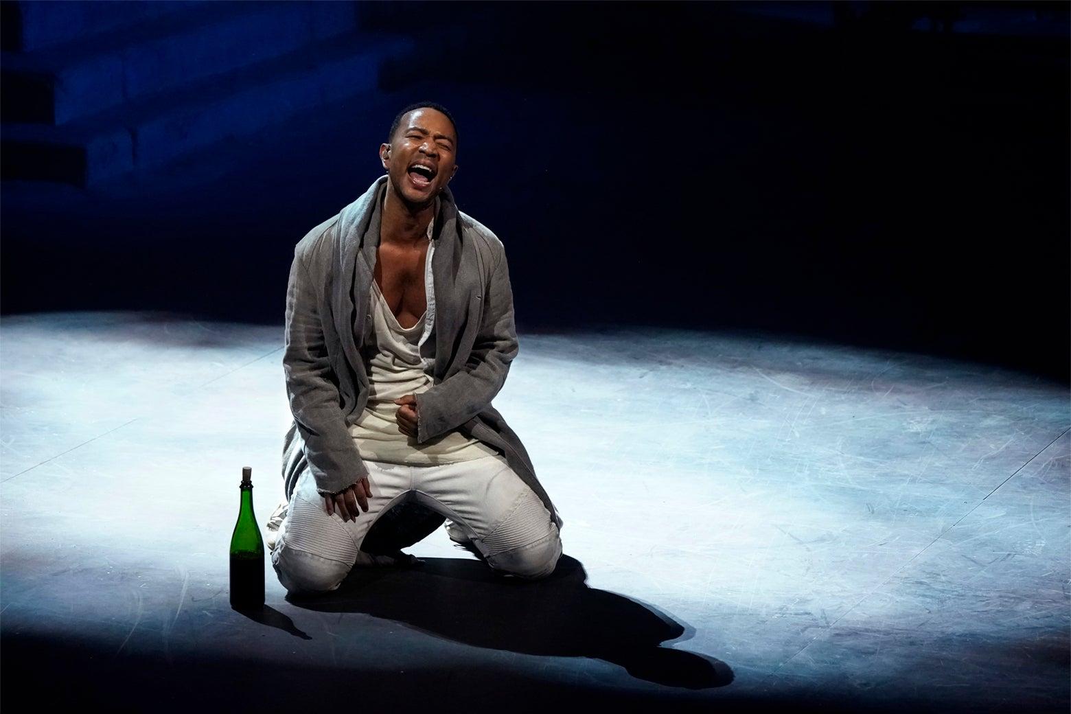 John Legend, in a photo taken during Jesus Christ Superstar Live in Concert, kneeling on stage and singing.