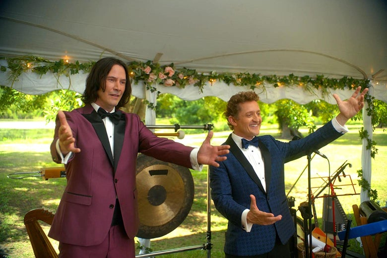 Keanu Reeves and Alex Winter stand in front of a gong and stretch out their hands in a scene from in Bill & Ted Face the Music