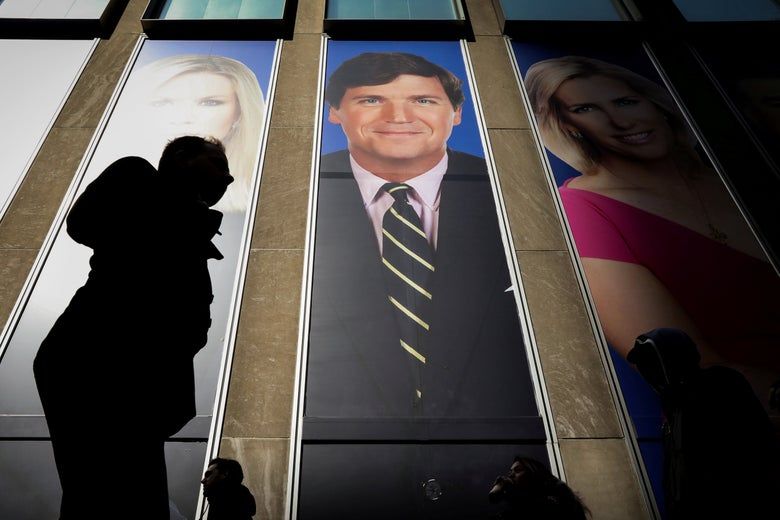 People pass by huge images of Tucker Carlson and other Fox News hosts on the News Corporation building in New York.