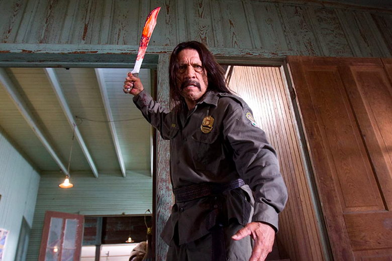 Danny Trejo, wearing a uniform and badge, brandishes a bloody machete.