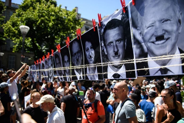 """A crowd passes underneath a clothesline pinned with black and white photographs of Emmanuel Macron, Joe Biden, and others, which have been altered to feature """"Hitler mustaches"""""""
