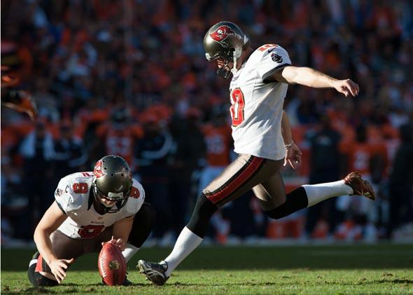 Punter Michael Koenen place-holds for kicker Connor Barth of the Tampa Bay Buccaneers during an extra point attempt against the Denver Broncos in December 2012.