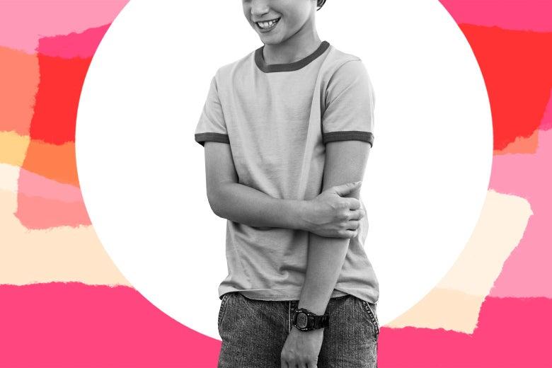 A teenage boy smiling sheepishly, alone.