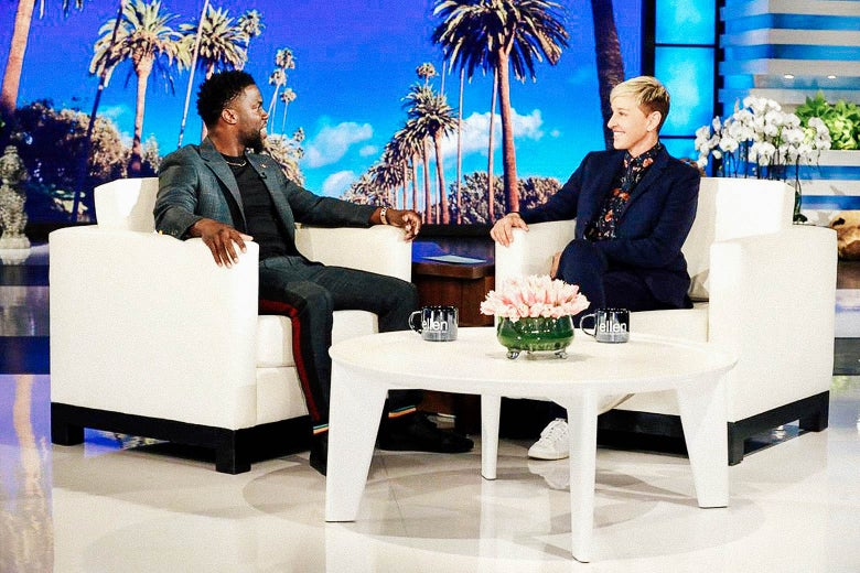 Kevin Hart and Ellen DeGeneres sit in white chairs on the set of her show.