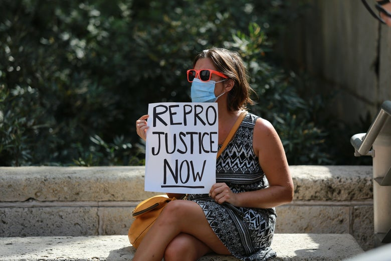 """A woman in a dress sits on a bench wearing a mask and sunglasses, holding a sign that says, """"REPRO JUSTICE NOW."""""""