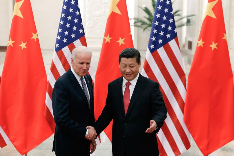 Biden and Xi shaking hands in front of U.S. and Chinese flags