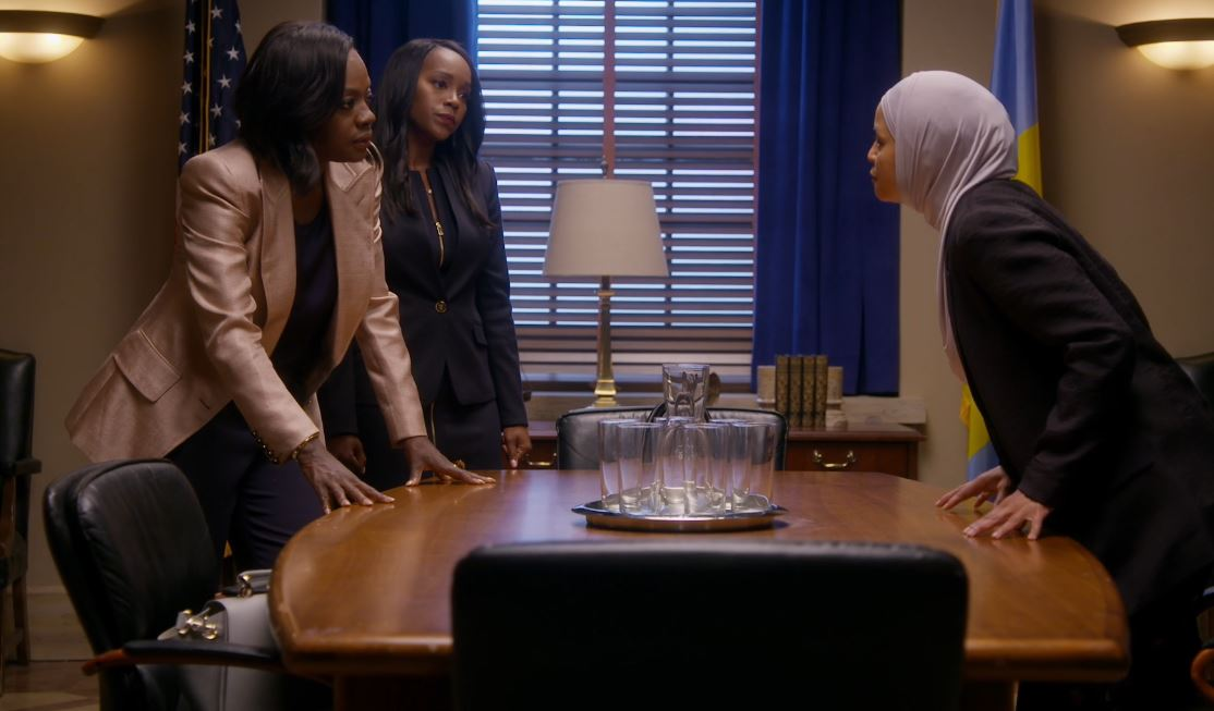 Three women lean over a conference table.