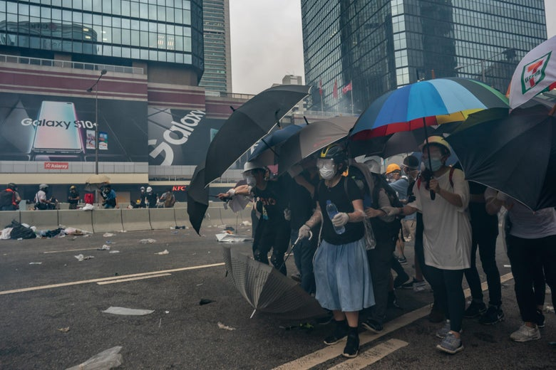 Protesters hold umbrellas as teargas is fired.