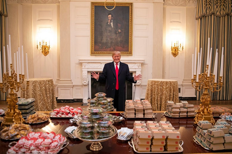 Donald Trump presides over a banquet table overflowing with fast food.