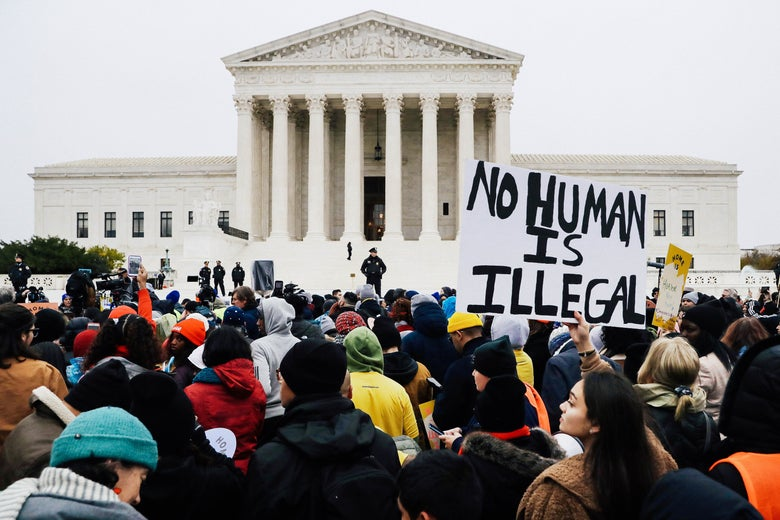 "A crowd of demonstrators outside the Supreme Court. One poster reads ""NO HUMAN IS ILLEGAL."""