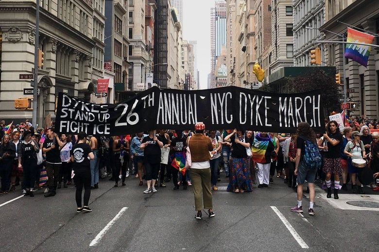 A view of the NYC Dyke March with a banner in the foreground.
