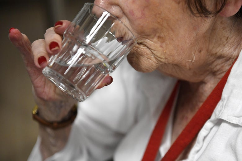 An old person drinks a glass of water in a retirement home on June 19, 2017 in Quimper, western France.