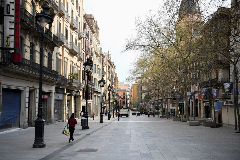 A Barcelona street, lined with shops, nearly empty. A lone woman walks away from the camera with a shopping bag.